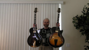 Donald Grass holding his two Conti archtop guitars