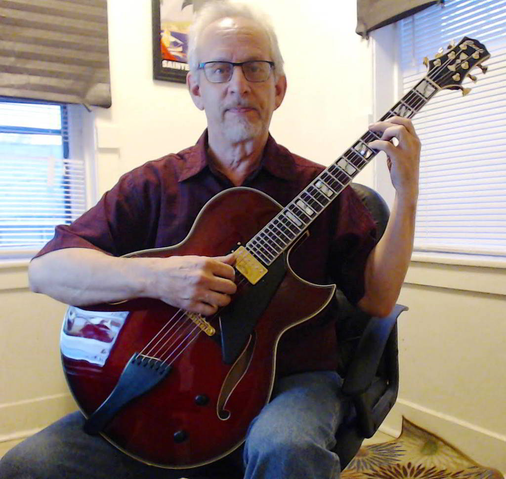 Bob Minchin holding his new Ruby Red Conti Heirloom archtop jazz guitar