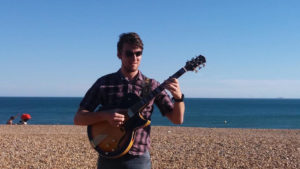 James Hopkins on the beach with his new Sunburst Conti Entrada Archtop Guitar